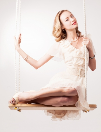beautiful young blond woman on a swing against light studio background photo