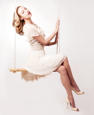 appealing attractive: beautiful young blond woman on a swing against light studio background Stock Photo