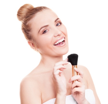 portrait of a beautiful woman applying makeup, isolated against white background photo