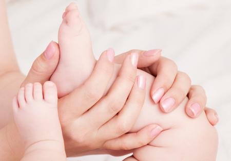 双生児の彼女の赤ん坊をマッサージの手 写真素材