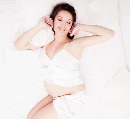 beautiful young pregnant woman waking up in bed at home   photo