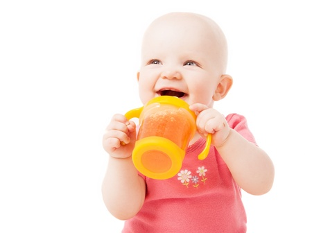 1 year old: happy one year old baby drinking juice, isolated against white background