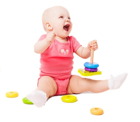 babies laughing: happy one year old baby playing with a pyramid, isolated against white background