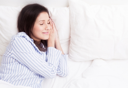 young brunette woman wearing pajamas on the white linen in bed at home, top view Stock Photo - 16367328