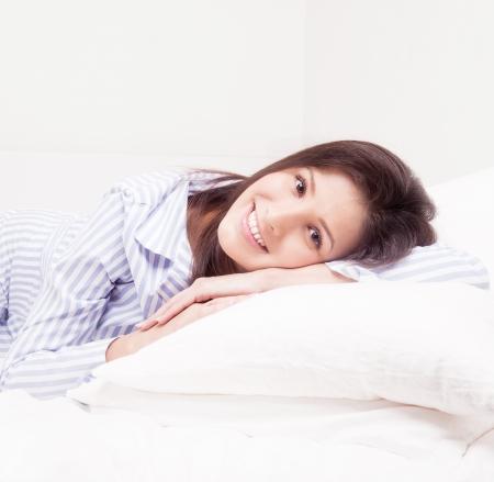 striped pajamas: joven morena en pijama en la ropa blanca en la cama en su casa, vista desde arriba