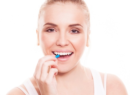 take medicine: pretty young woman holding a blue pill, isolated against white background