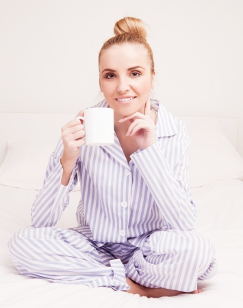 striped pajamas: beautiful young woman wearing pajamas drinking coffee in bed at home  Stock Photo