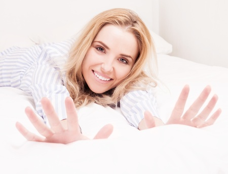 striped pajamas: beautiful young woman wearing pajamas wakign up and stretching  in bed at home