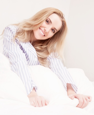beautiful young woman wearing pajamas wakign up and stretching  in bed at home  Stock Photo - 16466713