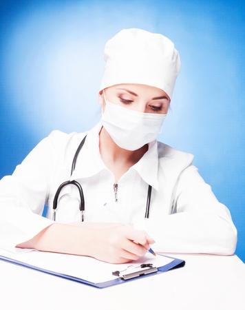 enfermera con cofia: retrato de mujer médico sentado a la mesa y por escrito, aislados en fondo blanco
