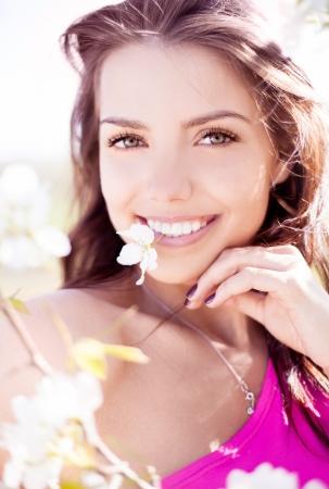 gyönyörű, fiatal, barna nő virággal a fogai áll közel az almafa egy meleg nyári napon