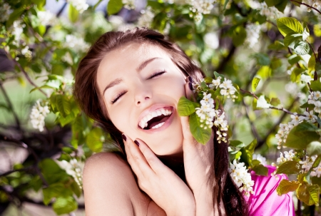 outsides: beautiful laughing brunette woman in the park on a warm summer day Stock Photo