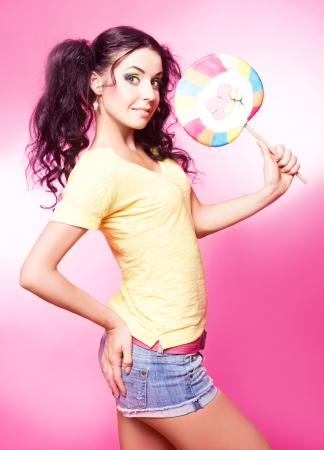 pretty young brunette woman with a lollipop, isolated against pink background photo