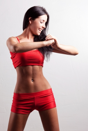 female sexuality: studio portrait of a young beautiful sporty woman, wearing red sports shorts and top  Stock Photo