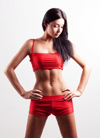 studio portrait of a young beautiful sporty woman, wearing red sports shorts and top  Stock Photo