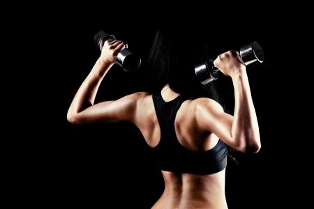 前後の若いブルネット スポーティな筋肉で働いている女性黒い背景に対して隔離される 2 つの金属ダンベルの手