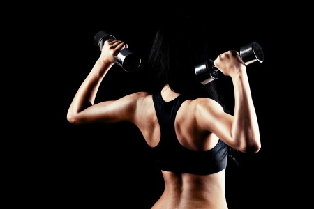female muscle: back and hands of a young brunette sporty muscular woman working out with two metal dumbbells, isolated against black background   Stock Photo