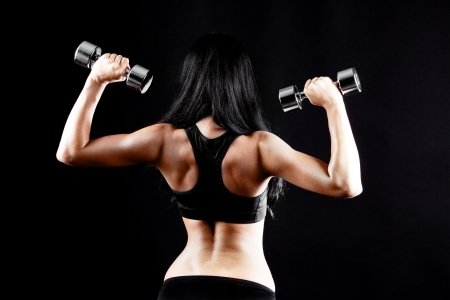 muscle tension: back and hands of a young brunette sporty muscular woman working out with two metal dumbbells, isolated against black background   Stock Photo