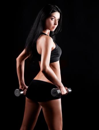 stúdió portré egy gyönyörű sportos izmos dolgozó nő ki két súlyzók, elszigetelt, ellen, fekete, háttér
