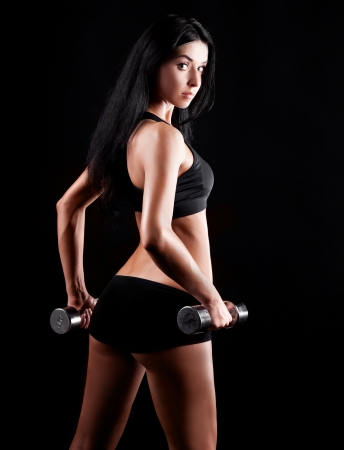 studio portrait of a beautiful sporty muscular woman working out with two dumbbells, isolated against black background