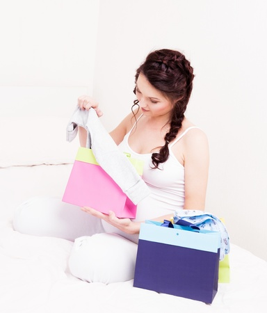 beautiful young pregnant woman with shopping bags and baby photo