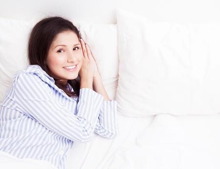 fiatal, barna nő pizsamában a fehér vászon ágyban otthon, felülnézet Stock fotó