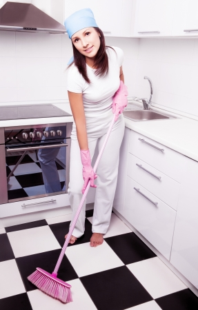 beautiful happy young housewife with a broom in the kitchen at home Stock Photo - 16671919