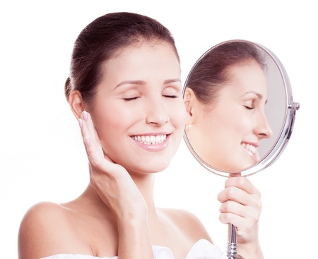 portrait of a happy beautiful woman looking into the mirror, isolated against white background Stock Photo - 16674838