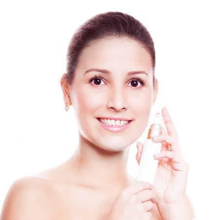 25 years old: portrait of a happy beautiful woman with a bottle of cream for face in her hands, isolated against white background