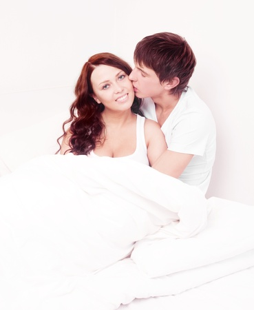 happy young beautiful couple in bed at home photo