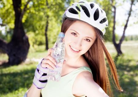 mujer joven que llevaba un casco con una botella de agua al aire libre Foto de archivo