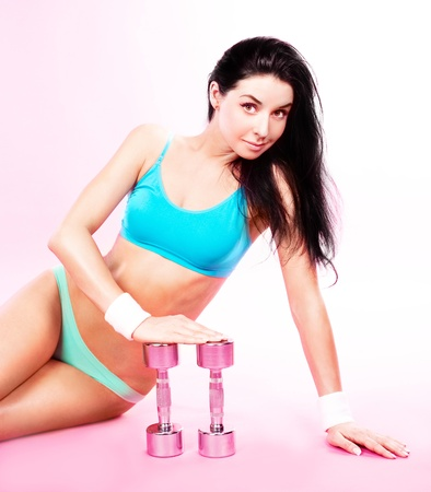 hands out: beautiful sporty young woman with dumbbells, against pink studio background Stock Photo