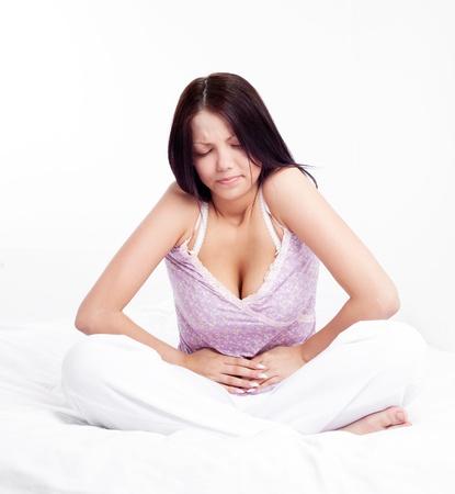 女性が自宅のベッドで胃の痛みを持っています。
