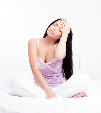 woman having a headache, in bed at home photo