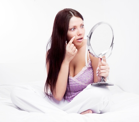 beautiful worried brunette woman having skin problems, with a mirror in bed at home Stock Photo - 16758087