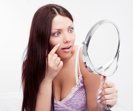 beautiful worried brunette woman having skin problems, with a mirror in bed at home photo