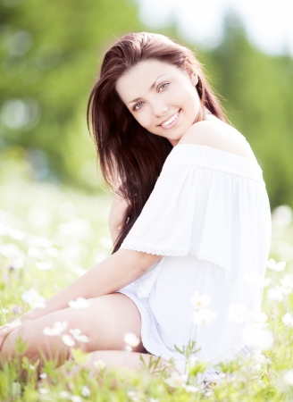 beautiful young brunette woman  on the  meadow with white flowers  on a warm summer day Stock Photo - 16772114