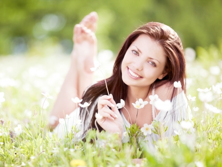 beautiful young brunette woman  on the  meadow with white flowers  on a warm summer day Stock fotó