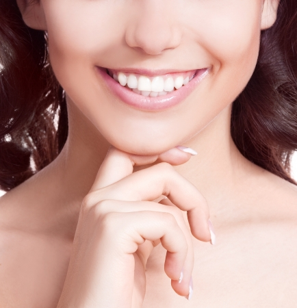 dental smile: closeup of the healthy white teeth of a woman, isolated against white background, copyspace for your text to the right