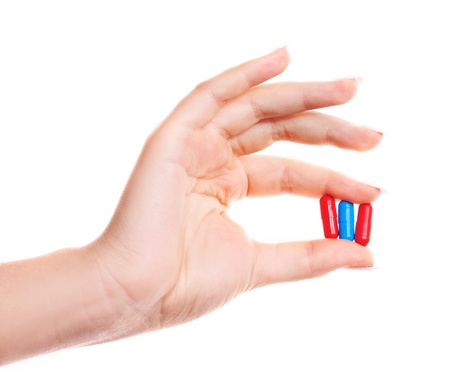 hand of a woman holding pills, isolated against white background photo