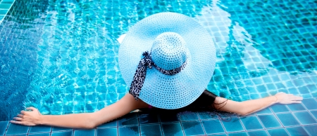 young woman wearing a blue hat sitting in the swimming pool Stock Photo - 16869443