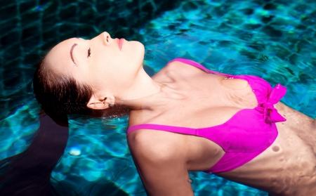 personas banandose: joven y bella mujer morena de relax en la piscina