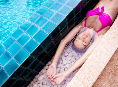 beautiful young brunette woman relaxing in the swimming pool  Stock Photo - 16869446