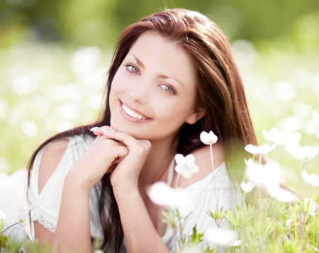 belle brunette: belle jeune femme brune sur le pré avec des fleurs blanches sur une chaude journée d'été