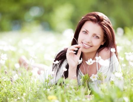 gyönyörű, fiatal, barna nő a réten, fehér virágokkal egy meleg nyári napon
