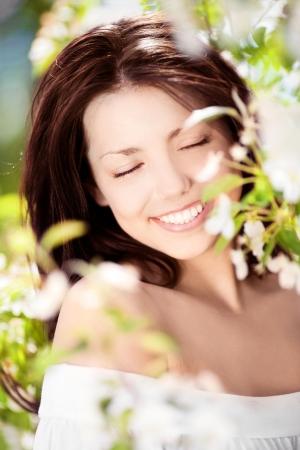 暖かい夏の日にリンゴの木の近くに立って美しい若いブルネットの女性