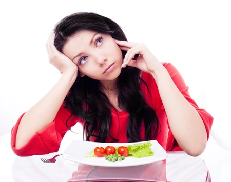 home keeping: upset young woman keeping a diet and eating vegetables in the kitchen at home Stock Photo