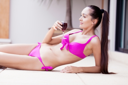 beautiful young brunette woman relaxing by the swimming pool with a glass of wine photo