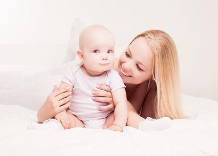 幸せな若い母と自宅のベッドで彼女の 1 歳の娘 写真素材