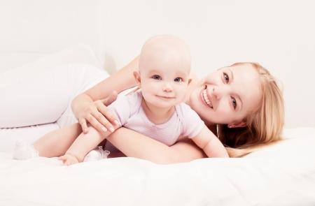 mama e hija: feliz madre joven y su hija de un a�o de edad en la cama en su casa Foto de archivo